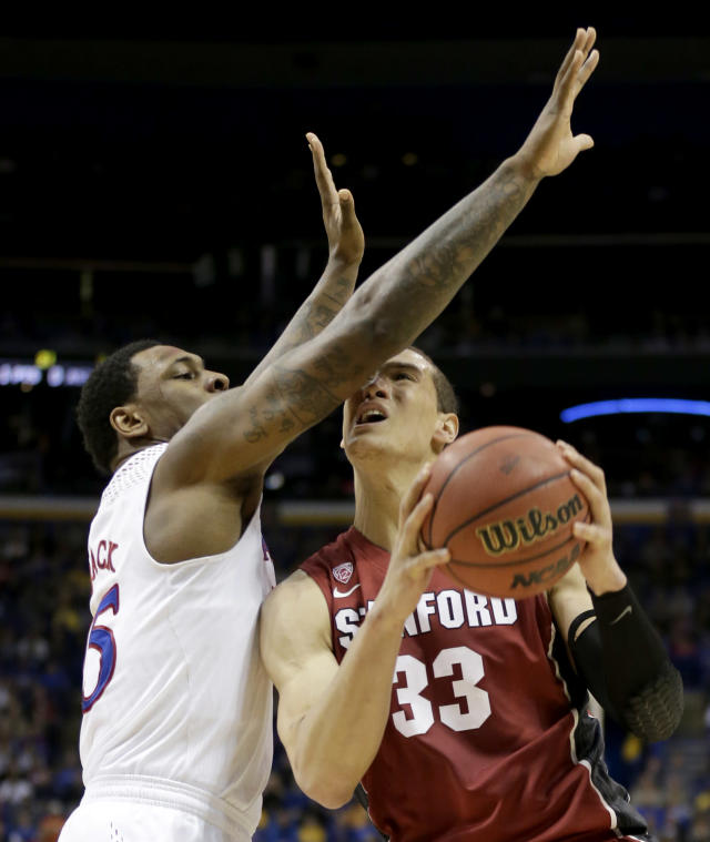 Stanford's Dwight Powell (33) shoots under pressure from Kansas's Tarik Black during the first half of a third-round game at the NCAA college basketball tournament Sunday, March 23, 2014, in St. Louis. (AP Photo/Charlie Riedel)