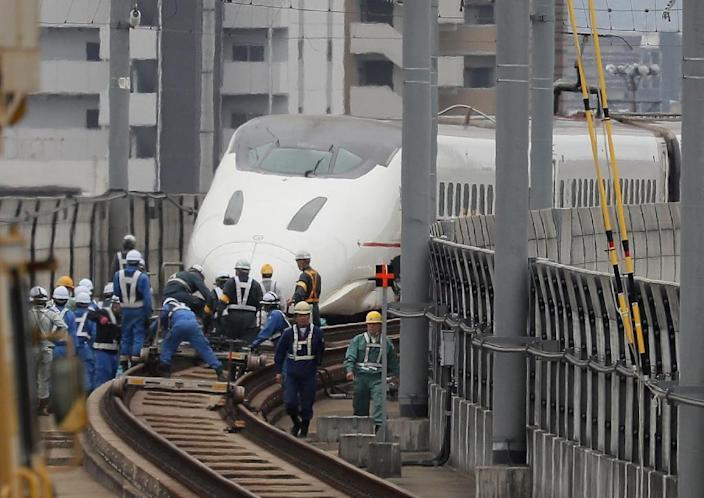 Railway workers fix the tracks of a Kyushu shinkansen (bullet train) after it derailed during the recent earthquakes in Kumamoto, on April 18, 2016 (AFP Photo/-)