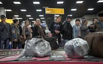 People, including passengers of a flight from the Turkmen capital Ashgabat, gather in the baggage claim area upon their arrival at Almaty International Airport, Kazakhstan April 5, 2019. Picture taken April 5, 2019. REUTERS/Mariya Gordeyeva