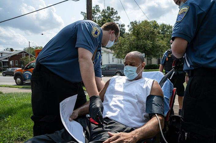 """<span class=""""caption"""">Emergency medical technicians aid a COVID-19 patient at his home in Louisville, Kentucky. Like much of the U.S., Louisville is experiencing an uptick in COVID-19 patients requiring emergency transport to medical facilities. </span> <span class=""""attribution""""><a class=""""link rapid-noclick-resp"""" href=""""https://www.gettyimages.com/detail/news-photo/members-of-louisville-metro-emergency-medical-services-tend-news-photo/1235239202?adppopup=true"""" rel=""""nofollow noopener"""" target=""""_blank"""" data-ylk=""""slk:John Cherry/Getty Images"""">John Cherry/Getty Images</a></span>"""