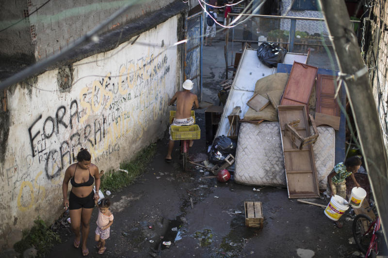 In this Jan. 9, 2014 photo, residents walk inside the Favela do Metro slum near Maracana stadium where people have been evicted and homes demolished in Rio de Janeiro, Brazil. The evictions and demolitions in this slum are part of urban renewal efforts launched ahead of this year's World Cup and the 2016 Olympics. (AP Photo/Felipe Dana)