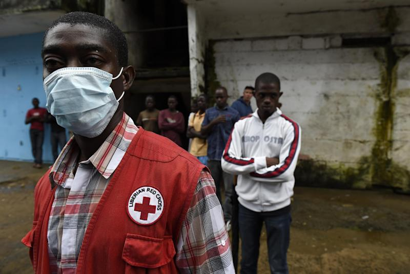 A Liberian Red Cross member looks for dead Ebola victims people in Monrovia on October 3, 2014 (AFP Photo/Pascal Guyot)