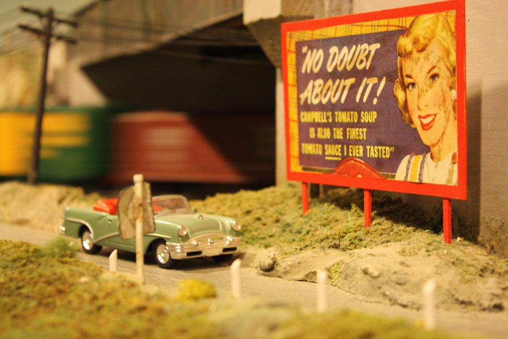 A train speeds by a 50s sign. After 67 years in the Liberty Village location, The Model Railroad Club of Toronto will be moving to make way for a condo.