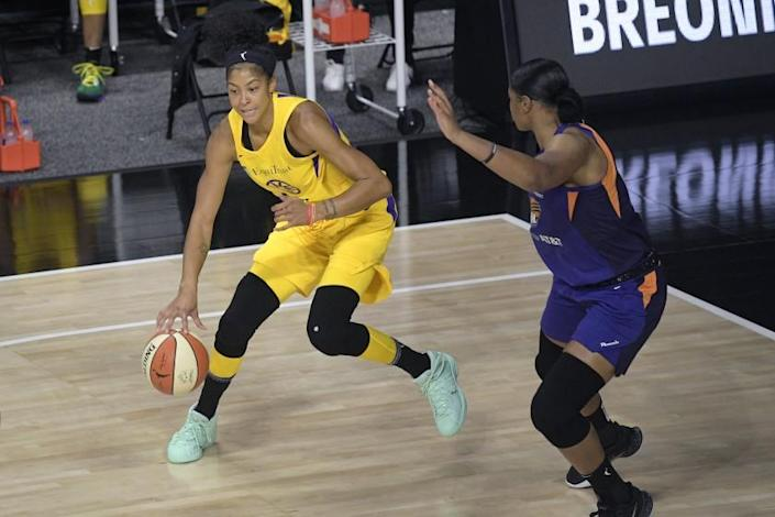 "Candace Parker, left, drives against Phoenix Mercury center Kia Vaughn during the first half Saturday. <span class=""copyright"">(Phelan M. Ebenhack / Associated Press)</span>"