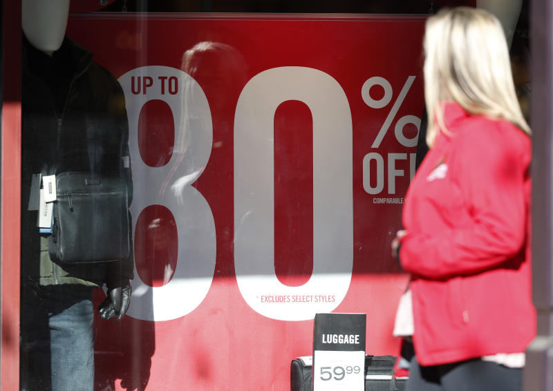 A placard advertises the discount available in a shop as last-minute shoppers finish up their Christmas gift lists at the Outlet Malls in Castle Rock Monday, Dec. 24, 2018, in Castle Rock, Colo. Retailers were offering ample discounts plus even more price cuts to those shoppers who ventured out with the holiday looming. (AP Photo/David Zalubowski)