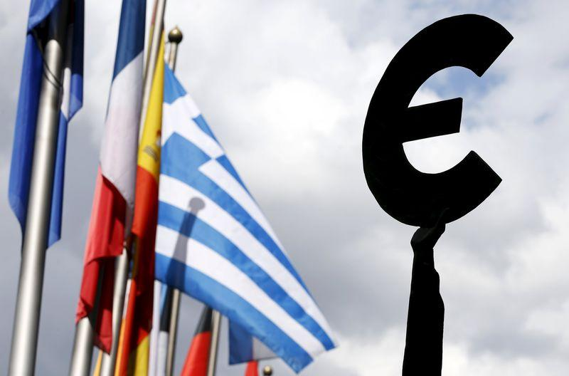 Greek flag flies behind a statue to European unity outside the EU Parliament in Brussels
