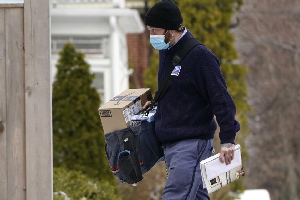 Postal carrier Josiah Morse delivers mail and packages, Wednesday, Feb. 3, 2021, in Portland, Maine. The U.S. Postal Service's stretch of challenges didn't end with the November general election and tens of millions of mail-in votes. The pandemic-depleted workforce fell further into a hole during the holiday rush, leading to long hours and a mountain of delayed mail. (AP Photo/Robert F. Bukaty)