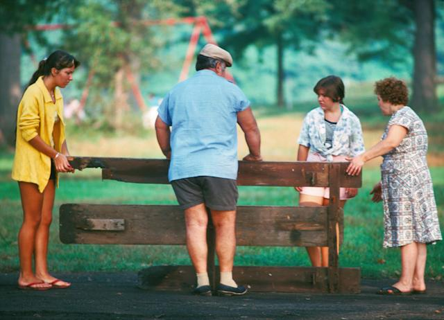 <p>Family salvages picnic table, unidentified Park. (Photograph by Ed Hausner/NYC Parks Photo Archive/Caters News) </p>