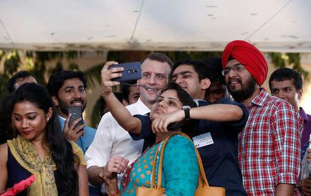 Students take selfies with French President Emmanuel Macron after a meeting in New Delhi, India, March 10, 2018. REUTERS/Adnan Abidi