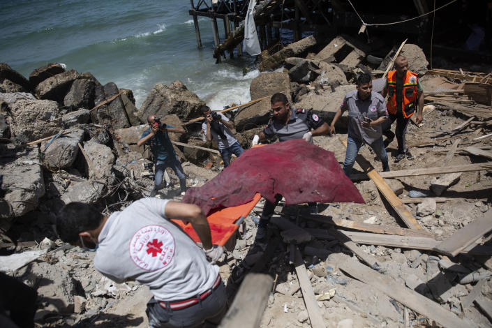 Palestinian rescue workers carry the remains of a man found next to a beachside cafe after it was hit by an Israeli airstrike, in Gaza City, Monday, May 17, 2021. (AP Photo/Khalil Hamra)