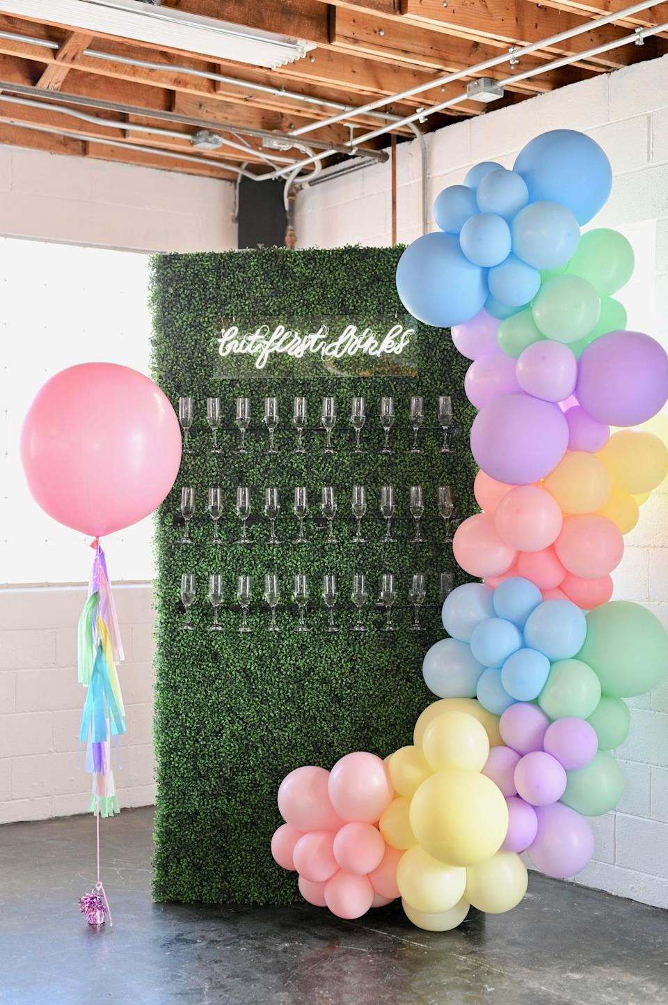 """<p>Make a <a class=""""link rapid-noclick-resp"""" href=""""https://www.popsugar.com/latest/DIY"""" rel=""""nofollow noopener"""" target=""""_blank"""" data-ylk=""""slk:DIY"""">DIY</a> drink wall with the help of a wooden board, plastic glasses, and clear shelving. Just glue the shelving in rows along the wooden board, add any decor you please (in this case, the couple used faux plants), and fill the glasses with the drinks of your choice before you place them onto the shelves.</p>"""