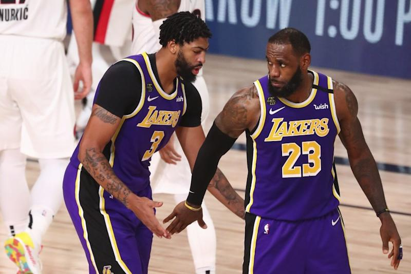 Los Angeles Lakers forward LeBron James (23) reacts after a dunk by forward Anthony Davis (3) in the second half against the Portland Trail Blazers in Game 3 of an NBA basketball first-round playoff series, Saturday, Aug. 22, 2020, in Lake Buena Vista, Fla. (Kim Klement/Pool Photo via AP)