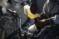 A man pours a small amount of gasoline into his motorcycle amid gas shortages in the La Saline neighborhood of Port-au-Prince, Haiti, Monday, July 19, 2021. The country of more than 11 million people are still reeling from the July 7 killing of President Jovenel Moise. (AP Photo/Matias Delacroix)
