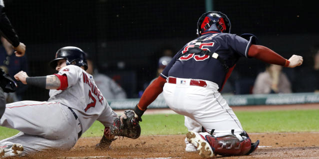 Boston Red Sox's Christian Vazquez, left, slides past the tag by Cleveland Indians catcher Roberto Perez, right, scoring on a ground-out by Rafael Devers in the third inning of a baseball game, Sunday, Sept. 23, 2018, in Cleveland. (AP Photo/Tom E. Puskar)