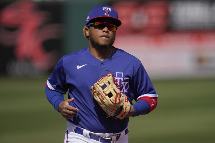 Texas Rangers left fielder Willie Calhoun runs in from the outfield during the first inning of the team's spring training baseball game against the San Diego Padres, Thursday, March 4, 2021, in Surprise, Ariz. Calhoun, who got hit in the face by a fastball in a spring training game last year, says he no longer feels like flinching or bailing out on breaking pitches. (AP Photo/Sue Ogrocki)