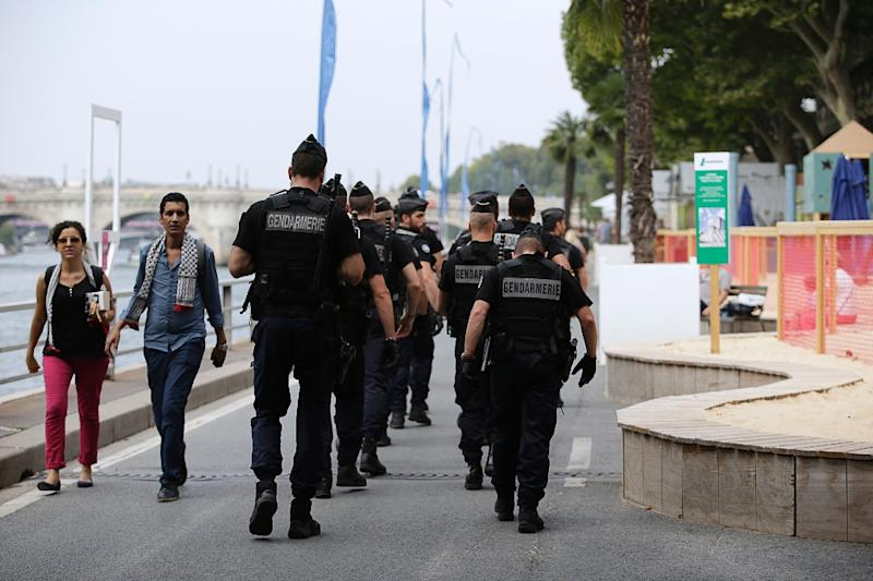 "Gendarmes walk on a quay alongside the Seine during the ""Gaza beach"" protest in Paris on August 13, 2015 (AFP Photo/Kenzo Tribouillard)"