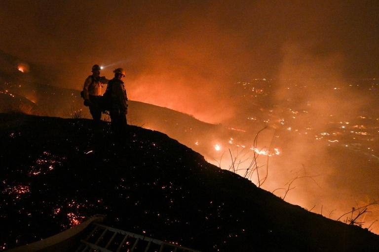 Firefighters look out over a burning hillside as they fight the Blue Ridge Fire in Yorba Linda, California