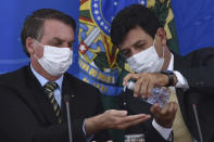 Wearing masks, Brazil's Health Minister Luiz Henrique Mandetta, right, applies alcohol gel on hands of President Jair Bolsonaro's hands during a press conference on the new coronavirus, at the Planalto Presidential Palace in Brasilia, Brazil, Wednesday, March 18, 2019. For most people COVID-19 causes mild or moderate symptoms. For others, especially the elderly and people with existing health problems, it can cause many other serious illnesses, including pneumonia. (AP Photo/Andre Borges)