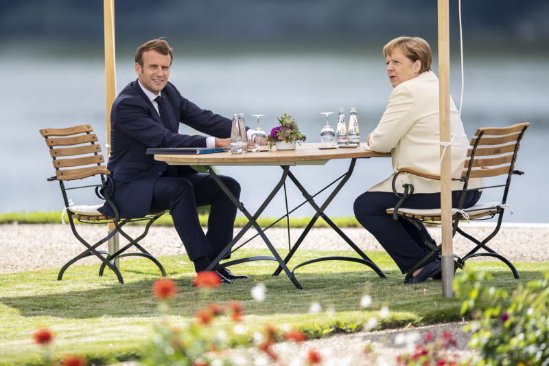 GRANSEE, GERMANY - JUNE 29: German Chancellor Angela Merkel and French President Emmanuel Macron sit in the garden as they meet in the grounds of Schloss Meseberg on June 29, 2020 in Gransee, Germany. The German Chancellor and French President will meet to discuss European Union funding during the Coronavirus pandemic. (Photo by Maja Hitij - Pool / Getty Images)