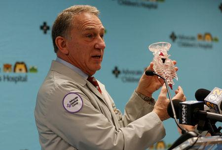 "Frank A. Vicari, MD, pediatric plastic/reconstructive surgery, holds a model representing two spines of ""Baby Dominique"" as he speaks during a news conference where doctors and staff discuss the outcome of a complex surgical procedure to treat the 10-month old, who was also born with four legs, at Advocate Children's Hospital in Park Ridge, Illinois, U.S., March 21, 2017. REUTERS/John Gress"
