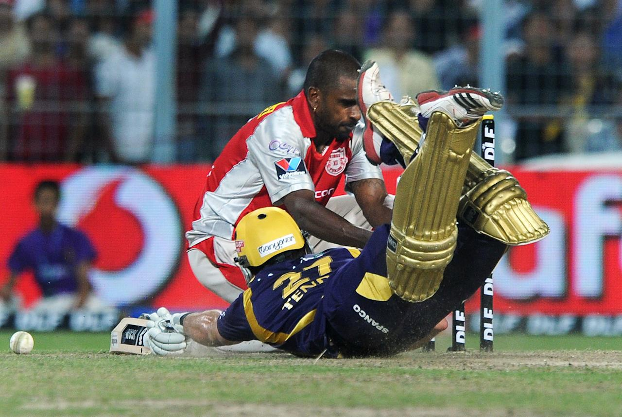 Kings XI Punjab bowler Dimitri Mascarenhas (back) attempts a run out as Kolkata Knight Riders batsman Ryan ten Doeschate (front) dives to make his ground during their IPL Twenty20 cricket match between Kolkata Knight Riders and Kings XI Punjab at The Eden Gardens in Kolkata on April 15, 2012. RESTRICTED TO EDITORIAL USE. MOBILE USE WITHIN NEWS PACKAGE. AFP PHOTO/Dibyangshu SARKAR (Photo credit should read DIBYANGSHU SARKAR/AFP/Getty Images)