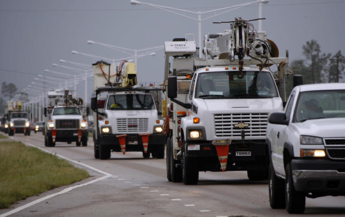 A steady armada of utility service trucks drive through Waveland, Miss., to assist  residents left without power from Hurricane Isaac, Thursday, Aug. 30, 2012. Signs of life returned to the Mississippi Gulf Coast on Thursday as curfews were lifted and some businesses and roads reopened, but many residents still couldn't make it home because of flooding in low lying areas and along rivers. (AP Photo/Rogelio V. Solis)