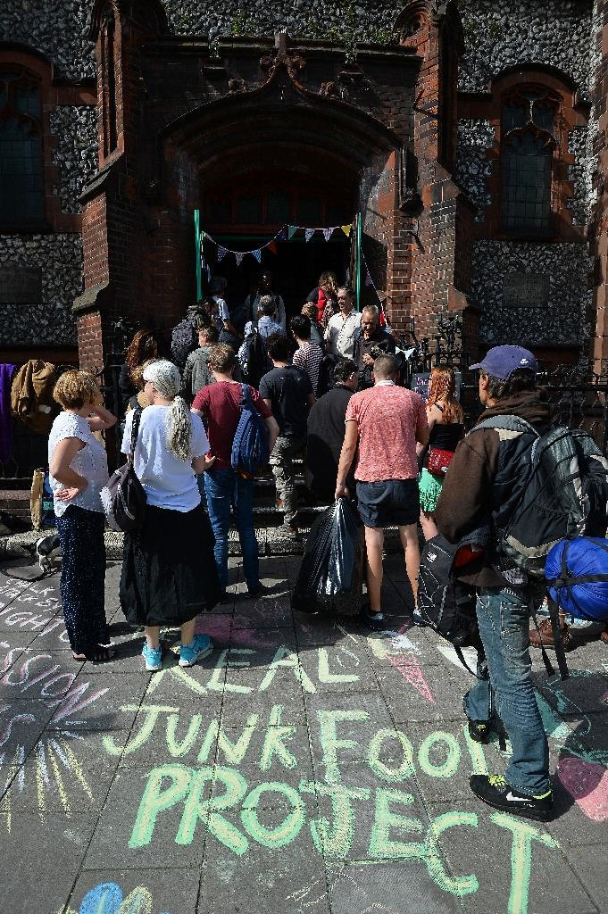 People queue to enter a Real Junk Food Project (RJFP) cafe in a church in Brighton, southeast England, on September 11, 2015 (AFP Photo/Glyn Kirk)