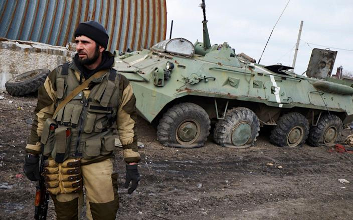 A pro-Russian fighter from Chechnya stands near a damaged Ukrainian armoured vehicle - Getty