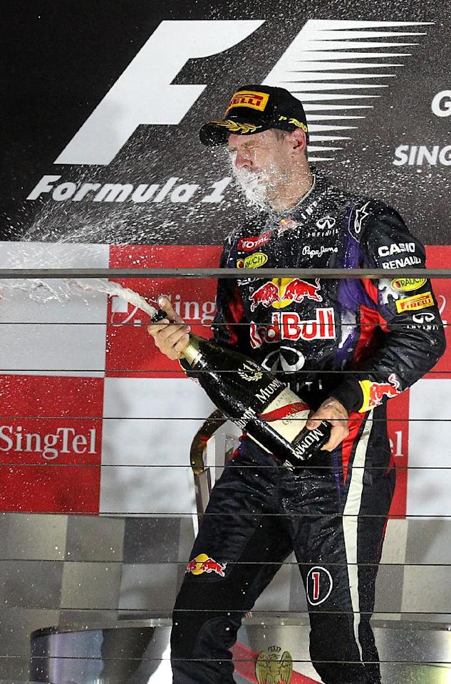 Red Bull driver Sebastian Vettel of Germany is sprayed in the face with champagne as he celebrates on the podium after winning the Singapore Formula One Grand Prix on the Marina Bay City Circuit in Singapore, Sunday, Sept. 22, 2013.(AP Photo/Wong Maye-E)