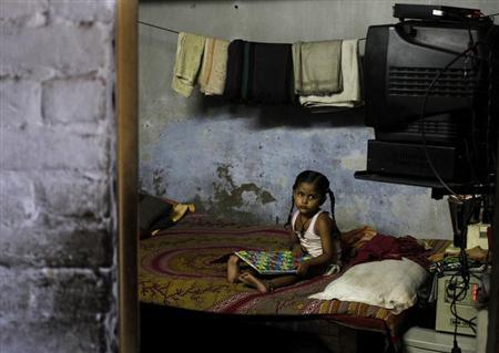 A girl plays a game inside her home at a slum in New Delhi September 23, 2013. REUTERS/Anindito Mukherjee/Files