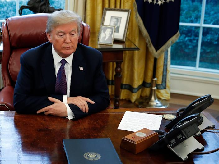 President Donald Trump sits at the Resolute Desk after signing Section 201 actions in the Oval Office of the White House in Washington, Tuesday, Jan. 23, 2018.