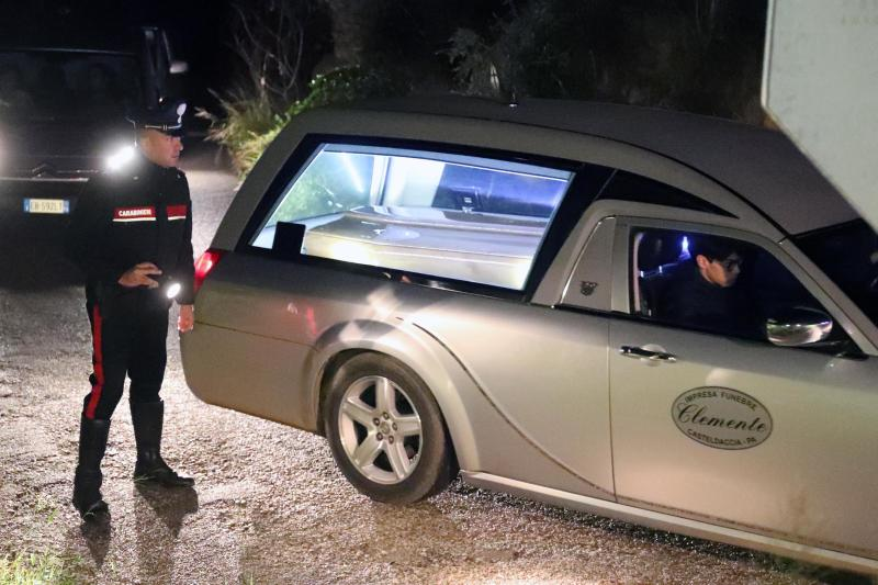 A Carabinieri (Italian paramilitary police) officer stands by a car carrying the coffin of one of the nine people that lost their lives when their home was flooded in Casteldaccia, near Palermo, Italy, Sunday, Nov. 4, 2018. Italian state radio says a rain-swollen river in the countryside near Palermo, Sicily, has flooded a home, killing 9 people. It said one person survived the flood late Saturday night by clinging to a tree, and that the victims were from two families spending the weekend together. (Igor Petyx/ANSA via AP)