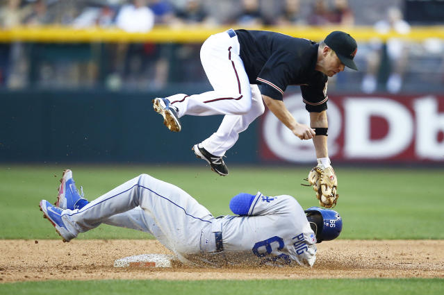 Los Angeles Dodgers' Yasiel Puig, bottom, slides safely into second base under the tag of Arizona Diamondbacks' Aaron Hill in the third inning of a baseball game on Saturday, April 12, 2014, in Phoenix. (AP Photo/The Arizona Republic, Rob Schumacher)