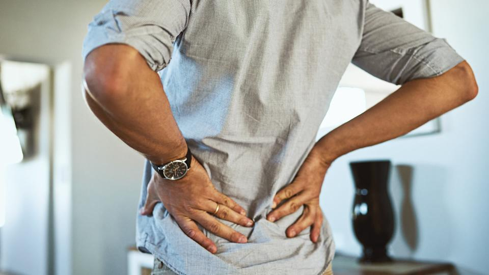 Rearview shot of an unrecognizable man holding his back in discomfort due to pain inside at home.