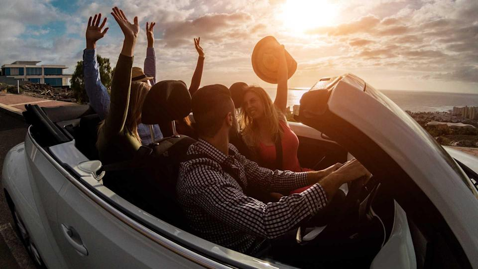 Happy young adults enjoying convertible car in summer