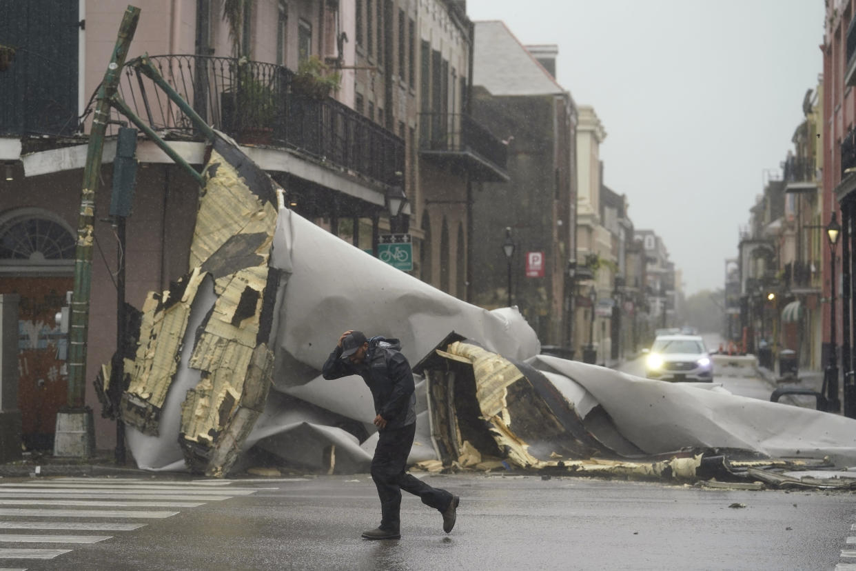 A man walks through a rainy intersection littered with mangled wrought iron railing, bent street pole and a section of roof that was blown off of a building.