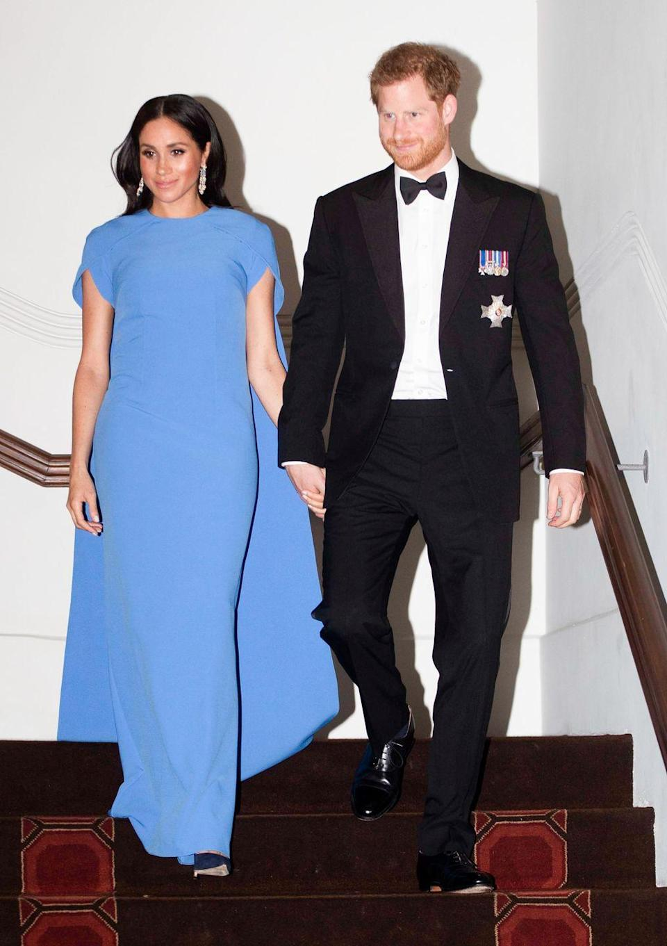 <p>Meghan clearly loves a Safiyaa cape dress. She chose this powder blue option for a 2018 state dinner in Suva, Fiji. The Duchess let the blue hue take center stage, pairing the dress with dangling earrings and a loose, wavy hairstyle. </p>