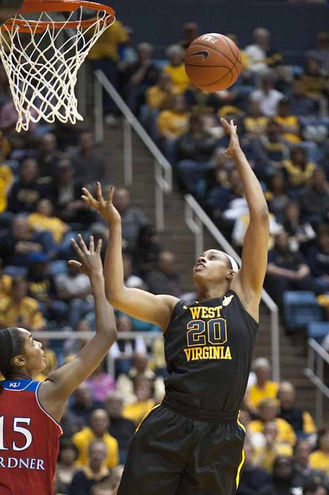 West Virginia's Asya Bussie (20) drives to the basket over Kansas' Chelsea Gardner during the second half of an NCAA college basketball game against Kansas, Tuesday, March 4, 2014, in Morgantown, W.Va. West Virginia won 67-60. (AP Photo/Andrew Ferguson)