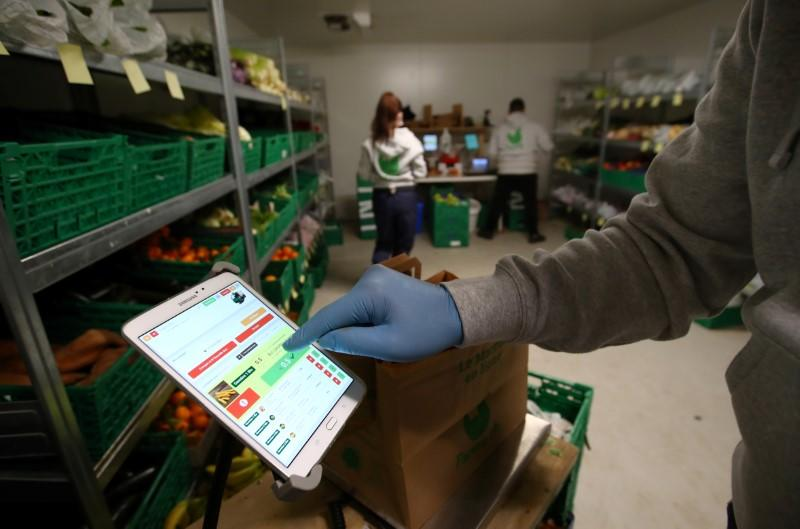 A member of staff of Farmy.ch, an online shop for home delivery of regional and organic products, wear gloves and prepares customers orders during the coronavirus