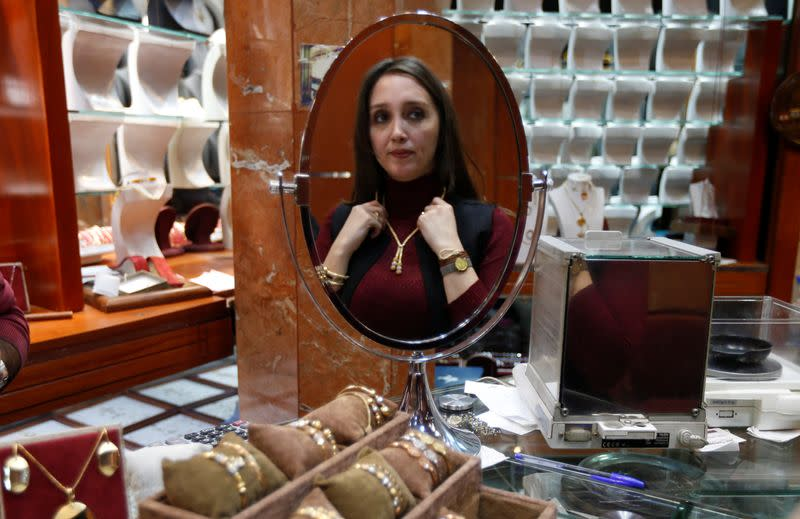 A woman is reflected in a mirror as she tries on a necklace at a jewellery shop in Beirut