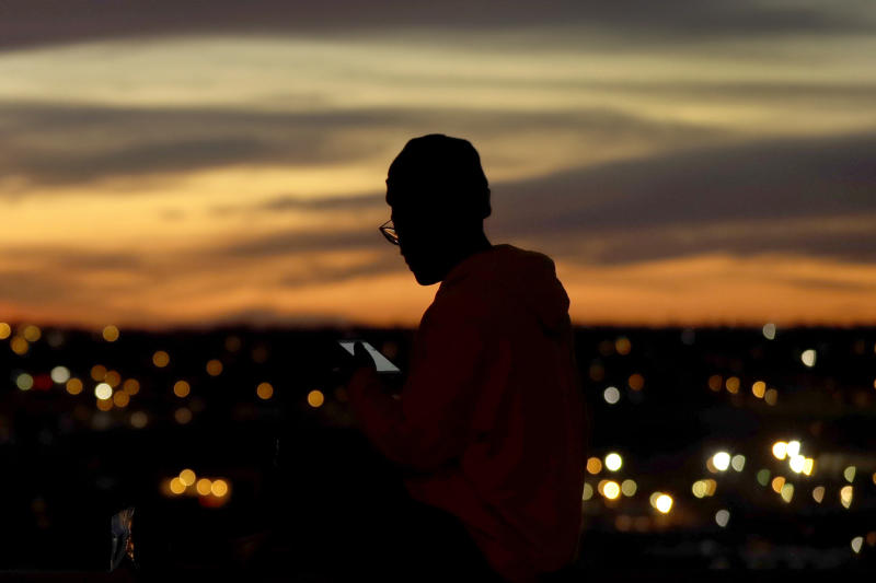 FILE - In this March 25, 2020, file photo, a person looks at a phone as the sun sets, in Kansas City, Mo. The city along with neighboring counties is under Stay at Home orders to help prevent the spread of COVID-19, the disease caused by the new coronavirus. (AP Photo/Charlie Riedel, File)