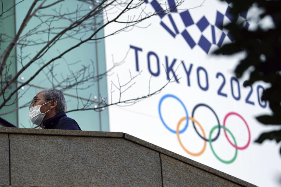 A man wearing a protective mask to help curb the spread of the coronavirus walks near the banner for the Tokyo 2020 Olympic Games Thursday, Feb. 25, 2021, in Tokyo. The Japanese capital confirmed more than 340 new coronavirus cases on Thursday. (AP Photo/Eugene Hoshiko)