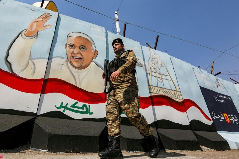 A member of the Iraqi security forces walks past a mural of Pope Francis with an Iraqi national flag, painted on a blast wall outside the Syriac Catholic Church of Our Lady of Deliverance in Baghdad