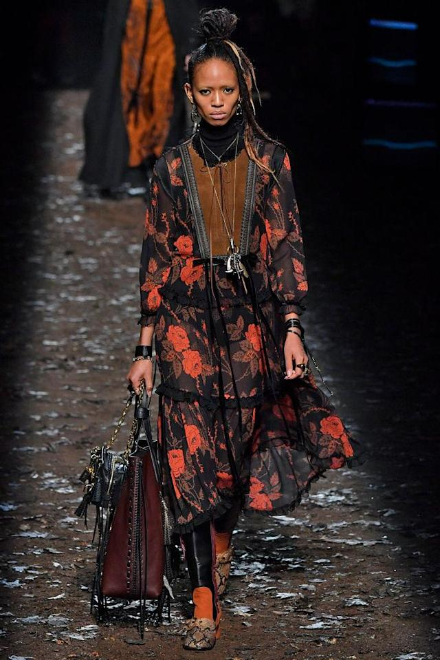 <p>Model wears an orange and black rose-print dress with a whipstitch and suede panel on the center of the dress. (Photo: Getty) </p>