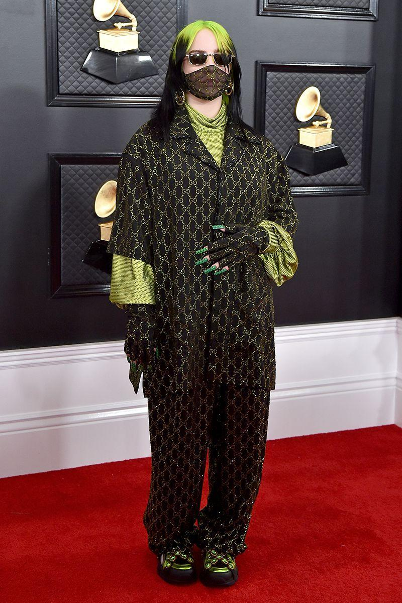 """<p>On the night that Billie accepted five Grammys, including Best New Artist, she opted for a pyjama-inspired Gucci suit with lime green metallic logos, complete with a mesh logo face mask and door-knocker earrings. <a href=""""https://www.cosmopolitan.com/uk/beauty-hair/celebrity-hair-makeup/a30673665/billie-eilish-grammys-makeup-2020/"""" rel=""""nofollow noopener"""" target=""""_blank"""" data-ylk=""""slk:Click here"""" class=""""link rapid-noclick-resp"""">Click here</a> to see all the makeup products her MUA used on the night. </p>"""