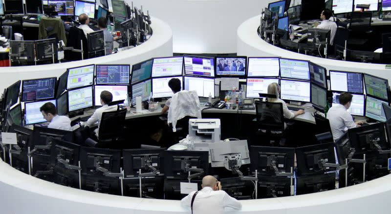 FILE PHOTO: Traders work at their desks in front of the German share price index, DAX board, at the stock exchange in Frankfurt