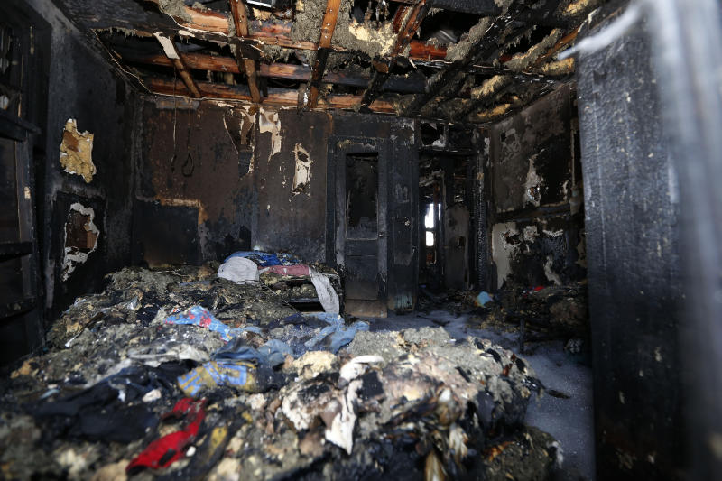 Burned clothes and the interior of a house are destroyed from a fatal fire on Saturday, Feb. 8, 2020 in Clinton, Miss. Authorities say a mother and her six children have been killed in the house fire in central Mississippi.  (AP Photo/Rogelio V. Solis)
