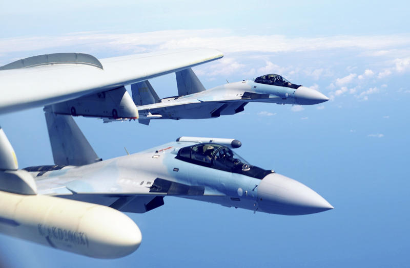 In this May 11, 2018, file photo released by Xinhua News Agency, two Su-35 fighter jets and a H-6K bomber from the People's Liberation Army air force fly in formation during patrol that included the Luzon Straits also known as Bashi Straits near Taiwan.  China has summoned the American ambassador and the defense attache and recalled its navy commander from a U.S. trip to deliver a strong protest against economic sanctions Washington lodged over the purchase of Russian fighter jets and surface-to-air missile equipment. The Defense Ministry says the U.S. had no right to interfere in Chinese military cooperation with Russia. The U.S. says the purchase of the weapons violates a law punishing Moscow for interfering in U.S. elections.  (Liu Rui/Xinhua via AP, File)