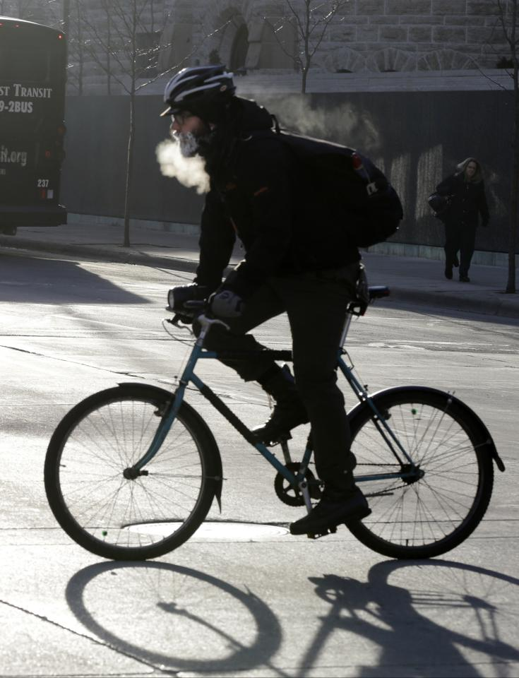 The breath of a bicyclist turns to steam and his beard frosts over as he bikes down the Nicollet Mall Tuesday, Jan. 22, 2013 in downtown Minneapolis where temperatures were in the double-digit, sub-zero numbers. (AP Photo/Jim Mone)