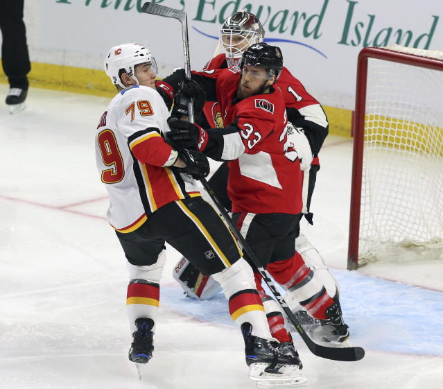 Ottawa Senators defenseman Fredrik Claesson (33) battles for position with Calgary Flames left wing Micheal Ferland (79) as Senators goaltender Mike Condon (1) looks on during the first period of an NHL hockey game in Ottawa, Friday, March 9 2018. (Fred Chartrand/The Canadian Press via AP)